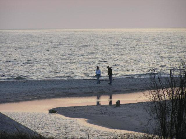 A happy couple strolls along the beach after eloping at Harkness Memorial State Park.